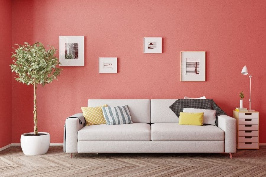 The living room shines bright with red wall and indoor plants